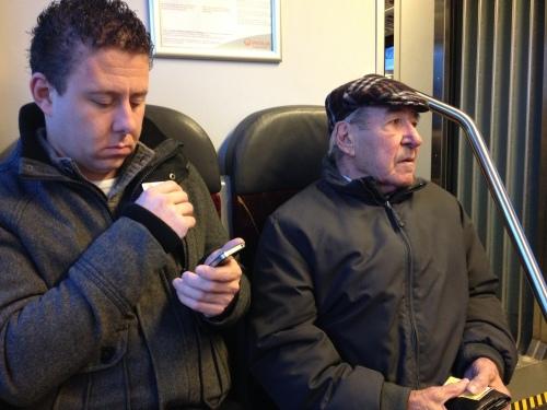 Twee werelden naast elkaar. De oude man bekijkt de wereld om zich heen, de jonge richt zijn blik op het scherm. Verleden en toekomst, zij aan zij