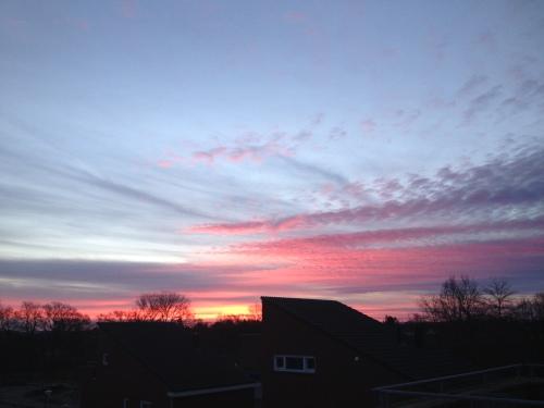 Vuurrod kleurt de hemel terwijl goudgele stralen langzaam over daken kruipt.