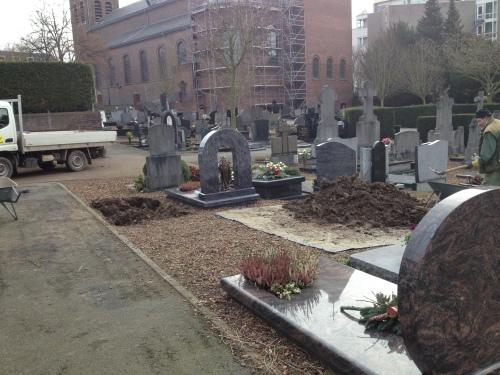 Een oud  rochelend mannetje vult het verse graf met aarde. Bloemen liggen verderop klaar. Ik blijf niet lang.