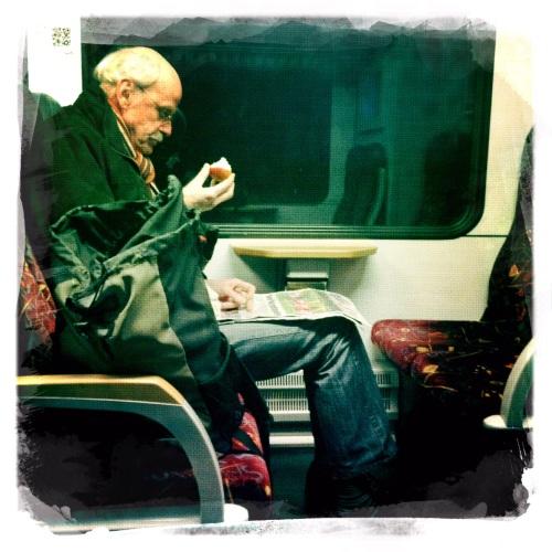 In het donker naar huis. De man met zijn appel, breeduit, geen aandacht voor de omgeving.