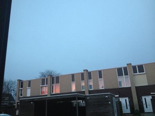 De ramen aan de overkant weerspiegelen het ochtendlicht. Ik weet wat me boven te wachten staat.