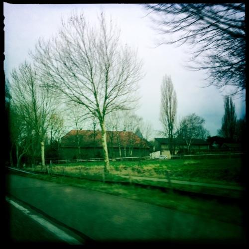 Per auto naar huis. Oude boerderijen verscholen in groen.
