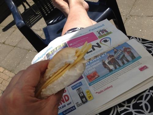 De zondagskrant brengt niet veel nieuws. Ik eet een broodje met mijn benen in de zon.