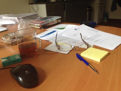 Aan het werk, papieren hier, papieren daar.