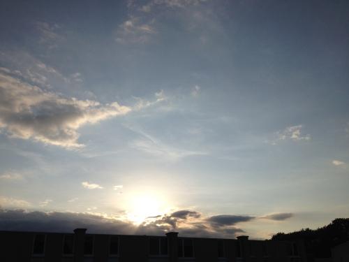 De zon is bijna verdwenen achter de huizen aan de overkant.